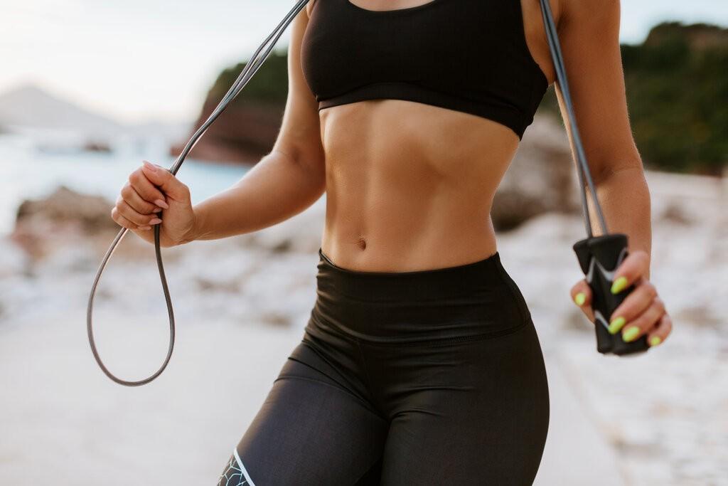 Жена тренира на плажа